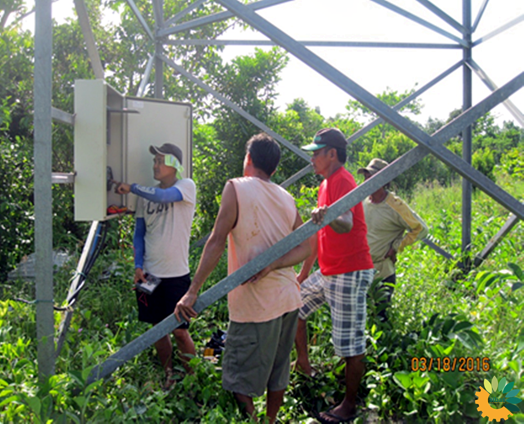 Local technicians checking on the controls of the solar pumping system.